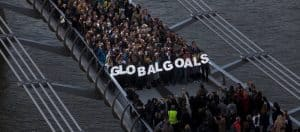 A group of people stand on a bridge holding large letters spelling 'Global Goals'.