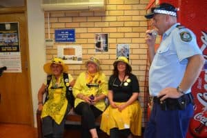 Three women known as the knitting nanas dressed in yellow and black clothing sitting on bench in police station. Police man with hands on his hips is standing to the left.