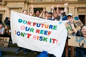 Photograph of students holding a banner reading 'Our Future, Our Reef, Don't Risk It'.