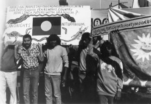 Protesters against Honeymoon Uranium mine, NSW, 1982. Aboriginal Australian protestors holding placards with Aboriginal flag.