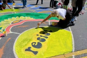 woman kneeling on the ground drawing in chalk the word resist inside yellow circle for a climate action in San Francisco