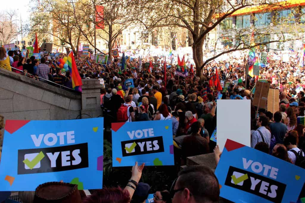A crowd of protestors at marriage equality rally. There are colourful rainbow flags, banners and in the foreground three people are holding signs that say Vote Yes with a green tick.