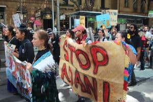 Female highschool walking in protest against inaction on climate change holding painted pandanus mat with words 'stop adani'.