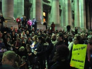 A crowd gathered in the evening, in the foreground a sign reads 'Shine a light on mental health'