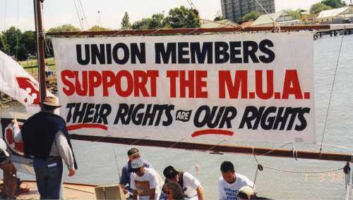Union members sitting by the water under sign that says - Union Members support the MUA - Their rights are our rights.