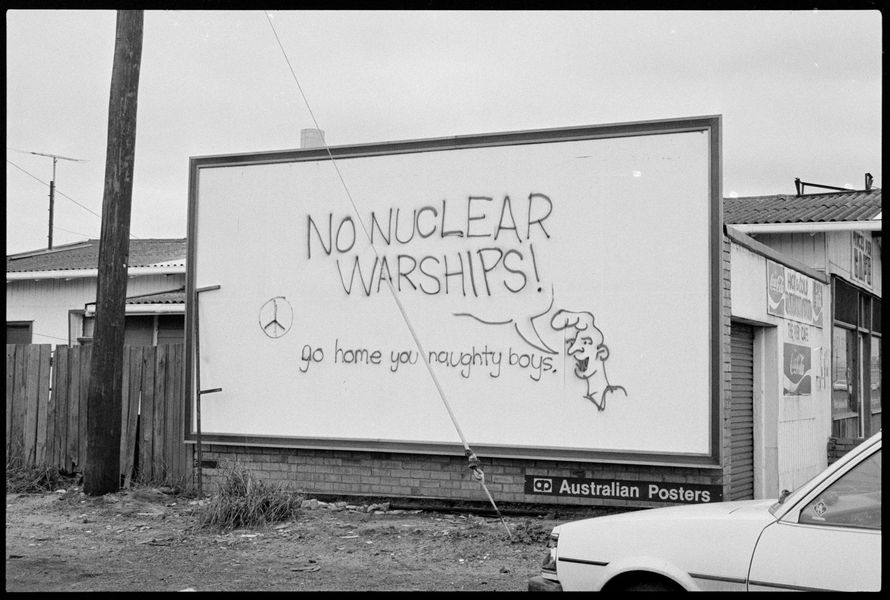 Billboard with a cartoon character and speech bubble says No Nuclear Warships Go home you naughty boys