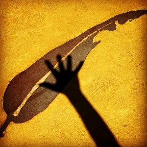 Photograph of a gum leaf design in the pavement with the shadow of a hand over it.