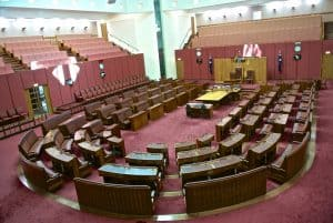 Photograph of the senate chamber showing maroon seats set up in a U shape.