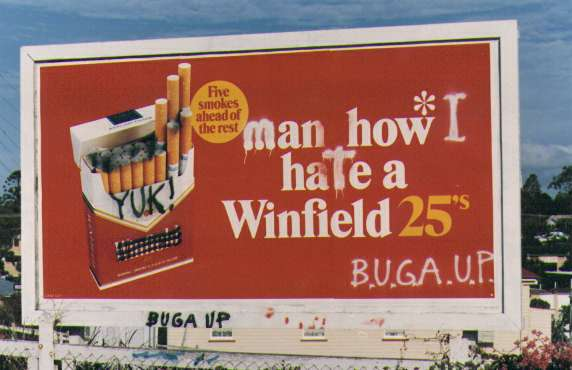 Photograph of a cigarette advertising billboard which has been modified. The new slogan reads 'man how I hate a Winfield 25', 'Yuk!', 'BUGA-UP'