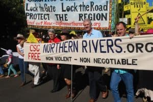 Protesters blockading at Bentley in NSW against the coal and gas industry in 2014. Protestors walking with banner that says CSC Free, Northern Rivers.org, Non-violent, Non negotiable and another banner that says Lock the Gate, Lock the Road, Protect the Region