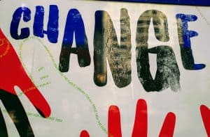 Photograph of hand drawn letters in blue and black on a white background. The word is 'Change'.