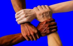 Close up photograph of four people gripping hands to wrists forming a solid square.