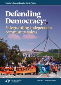 Cover of the Defending Democracy: Safeguarding independent community voices Report. Photograph of a people marching with climate and Indigenous rights banners and flags with Parliament House in the background.