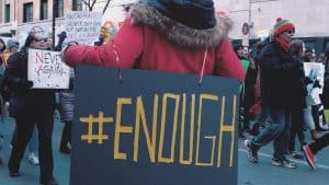 woman in protest carrying a sign saying #enough