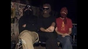 Three people sit wearing balaclavas.