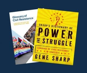 the covers of 2 publications - on left is Glossary of civil resistance with images of people protesting holding rainbow flag. On right is Sharp's dictionary of Power and Struggle with an illustration of a hand punching the air