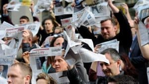 A crowd of people holding up newspapers with squares cut out for them to look through.