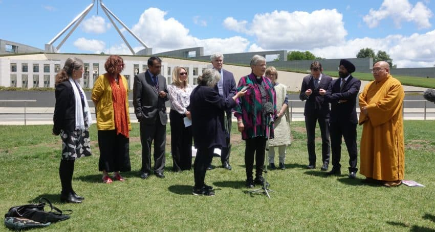 12 people standing in front of Australia's parliament. A speaker is stepped forward from the group, wearing a pastor's collar.
