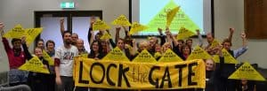 A group of people stand behind a Lock the Gate banner and hold yellow triangles in the air.
