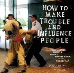 Cover of How to Make Trouble and Influence People. Features a photograph of someone in a sugar glider outfit being removed from an area by two policeman.