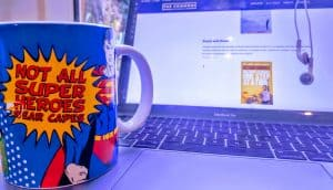 Mug sitting on laptop that says 'Not all super heroes wear capes'