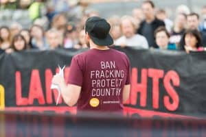 Man addressing anti-fracking rally in the Northern Territory, Australia wearing a tshirt that says 'Ban fracking Protect Country' with the logo SEED