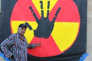 Uncle Kevin Buzzacott stands in front of a large banner depicting a black hand against a red and yellow nuclear symbol.