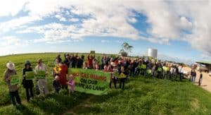 Photograph of a large group of people in a rural paddock. They are holding signs and banners reading 'No Gas Mining on Our Prime Ag Land'.