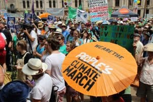 "people at climate change march with person holding orange parasol with words ""we are the people's climate march"""