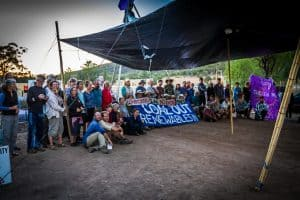A group of smiling protestors under a tarp shelter. A banner reads 'Coal Out, Renewables In'.