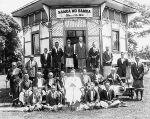 Black and white photograph of Mau leaders sitting in front of a building.