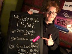 A young man with red hair and wearing glasses points to a blackboard sign titled 'Melbourne Fringe'. His finger points to the 'Sold Out' sticker next to 'Sustainable Standup'.