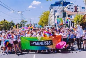 Photograph of a jubilant crowd of young people wearing 'Queer Pride' tshirts, standing behind a rainbow coloured Minus18 banner.