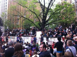 Photograph of the first General Assembly of Occupy Melbourne, October 15 2011. A large gathering of people in City Square with signs.