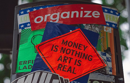 an outdoor post plastered with stickers with the writing organize and money is nothing art is real