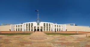 Photograph of the front of Australian Parliament House. The front paving shows a pattern that echoes Aboriginal artwork. The building is white with a flag spier and visible Australian flag blowing in the wind.