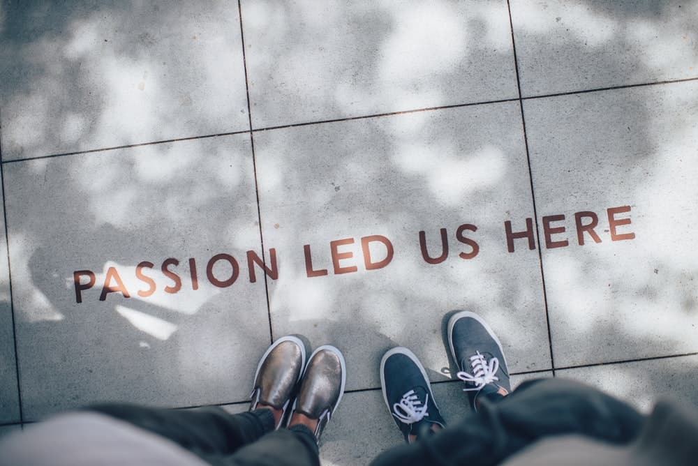 Photograph of two people standing on pavement, taken from above. Written on the ground is 'Passion Led Us Here'.