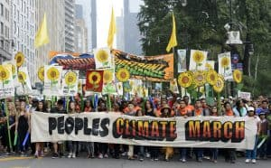 A large crowd marches behind a banner reading 'Peoples Climate March'. The march is led by First Nations people. Marchers hold colourful placards depicting sunflowers. A large banner is held high reading 'Frontlines of Impact, Forefront of Change'.
