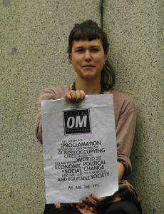 Woman holding poster that says Occupy Melbourne and We are the 99%