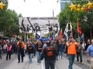 Protestors marching down the street holding banners. One large banner says AMWU Vehicle Workers