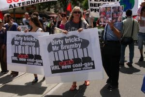 Protestors marching down street. Woman at front holding banner that says Dirty tricks, Mr Brumby -HRL new coal-gas power station