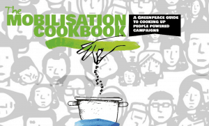 "Title page of the mobilisation cookbook, featuring the words 'Mobilisation Cookbook: A Greenpeace Guide to cooking up people powered campaigns"", over a background of diverse cartoon faces. Below the text is a cartoon of a cooking pot, with a hand sprinkling something granular into it."