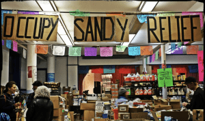 inside a room set up to help with occupy sandy relief. lots of boxes with food and people