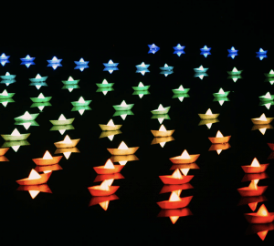 beautifully lit paper boats floating in the dark