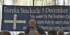 man standing in front of a eureka stockade flag giving a speech