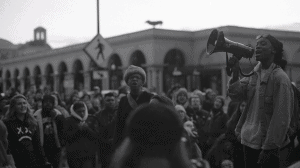 A black trans lives matter demonstration with the BQIC (Black Queer & Intersectional Collective) shutting down High Street in Columbus, OH. Person holding loudspeaker addressing a crowd on the street.