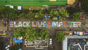 aerial shot of mural that says Black Lives Matter on road in between buildings in Seattle