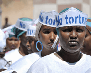 "Singers wearing hats advocating ""No Torture"" line up before performing at a Human Rights Day event outside of Mogadishu Central Prison in Somalia."