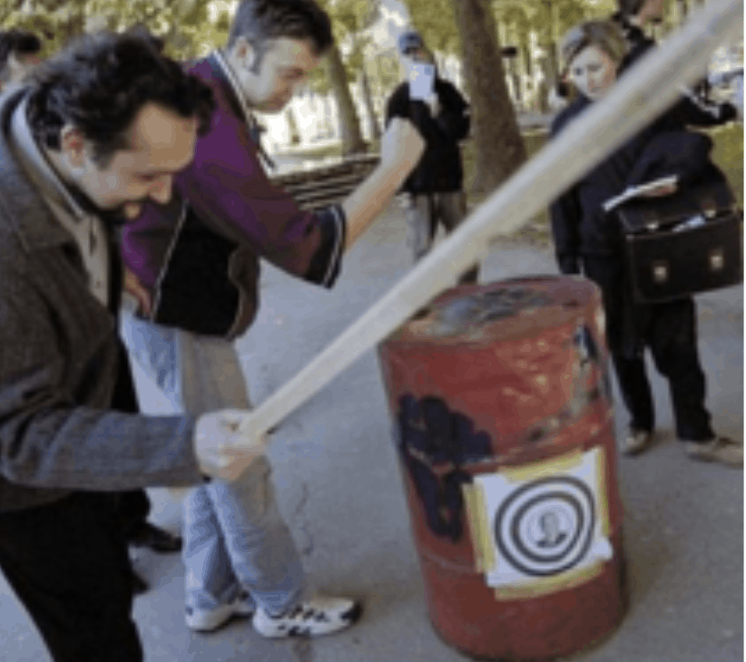 A man holding bat is about to hit a red barrel with Milosevic's face on it. There are bystanders watching in the background.