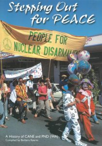 A group of people walking down the street holding banners and protesting. One big banner says Stepping Out for Peace, People for Nuclear Disarmament. Two protestors at the front are dressed in clown costumes.